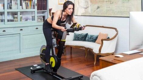 Mujer haciendo bicicleta estática en casa.