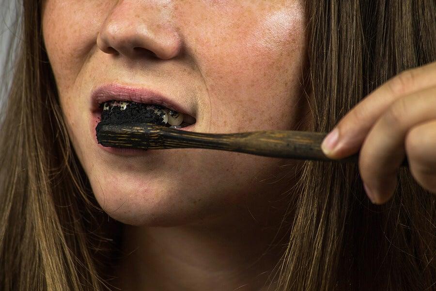 Mujer cepillándose los dientes con carbona activado.