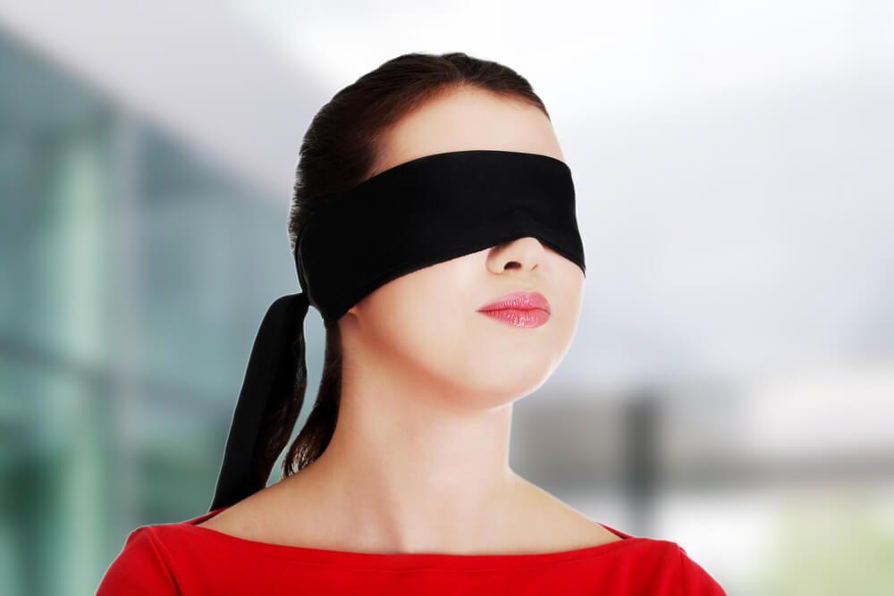 Mujer con venda en los ojos autoengañándose
