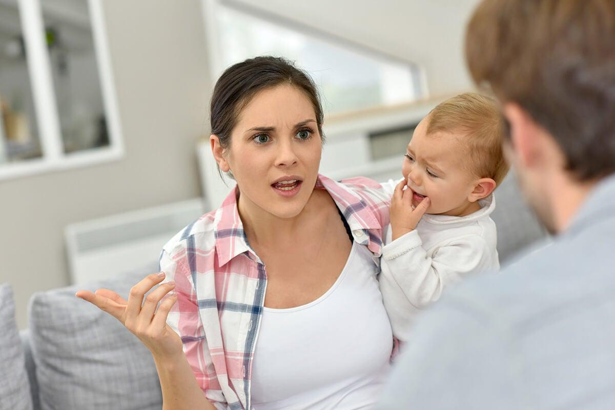 Mujer discutiendo con su hijo en brazos