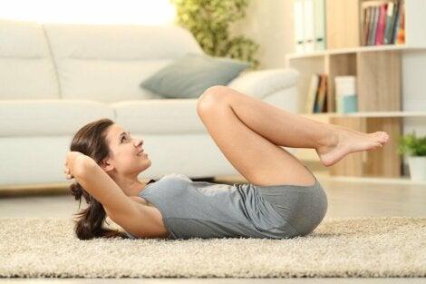 Mujer haciendo abdominales en casa.