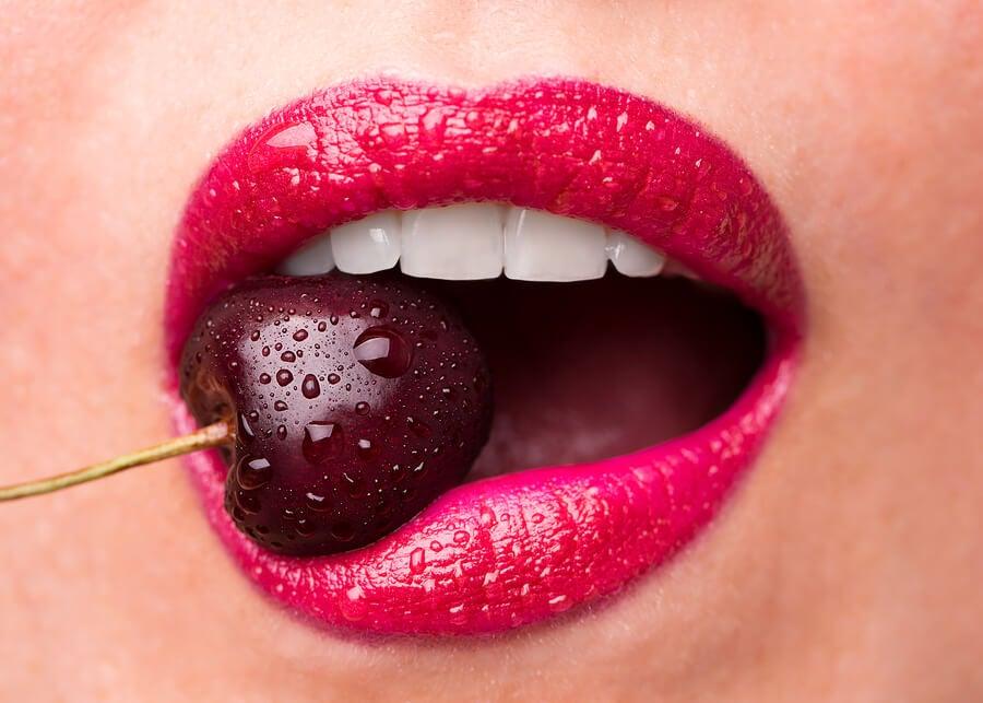 Mujer con pintalabios rojo mordiendo una cereza.
