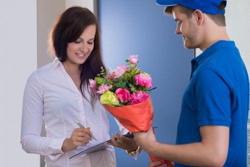Mujer recibiendo un ramo de flores a la puerta.
