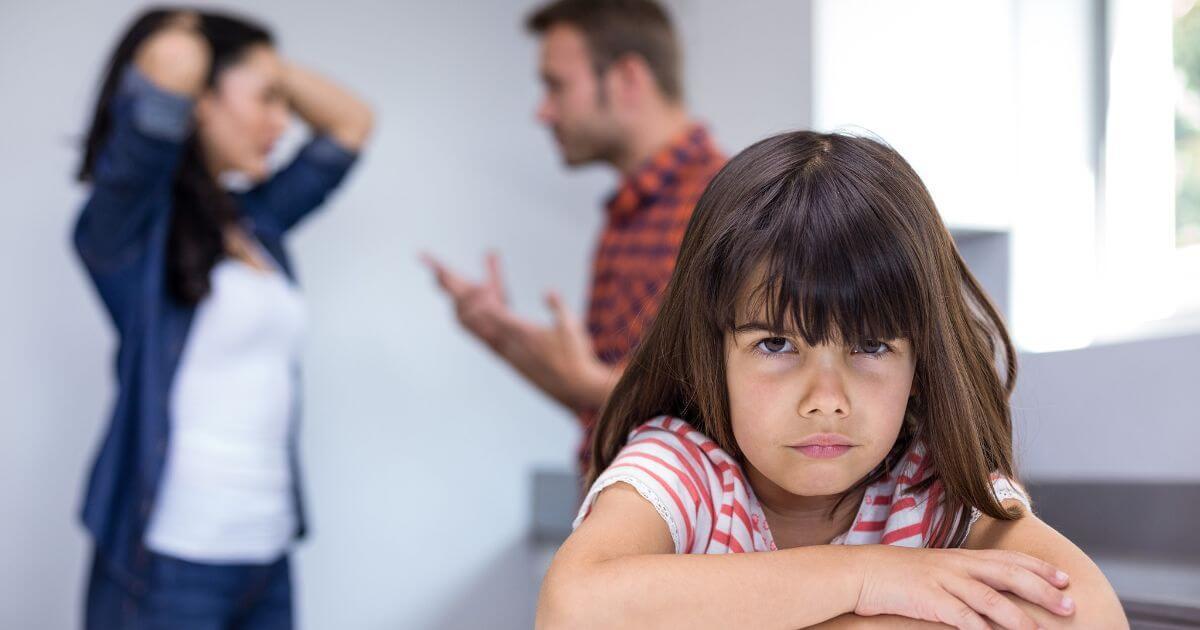 Niña con padres que discuten.