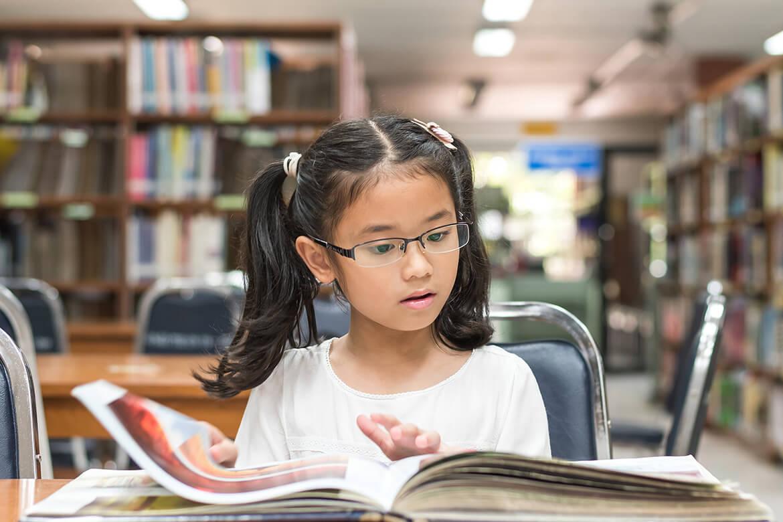 Niña pequeña lee un libro con fotografías en una biblioteca.