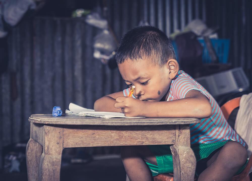Niño pobre estudiando