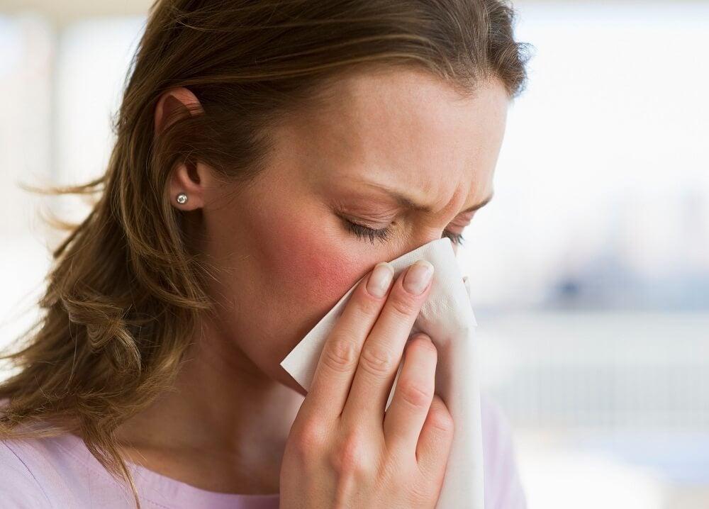 Mujer sonándose la nariz con un pañuelo.