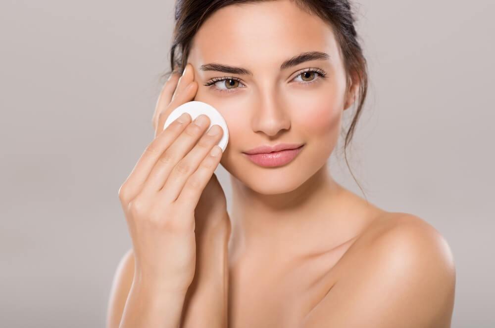 Mujer limpiándose la cara con un algodón.