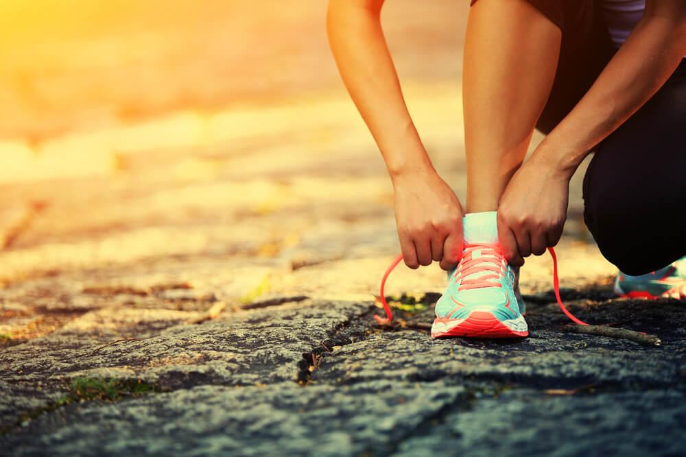 Persona atándose los cordones de la zapatilla deportiva para mantener su peso equilibrado mediante el ejercicio físico