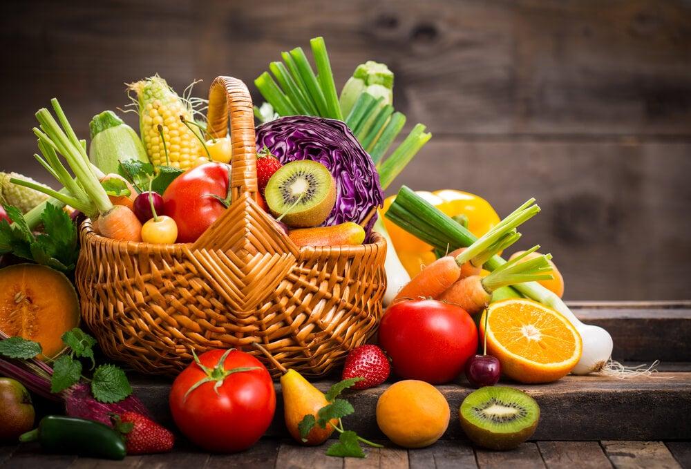 Cesta llena de alimentos saludables como verduras y frutas
