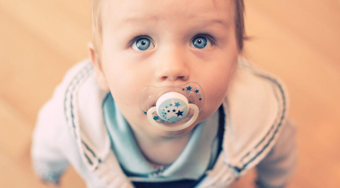 Bebé mirando hacia arriba mientras succiona el chupete