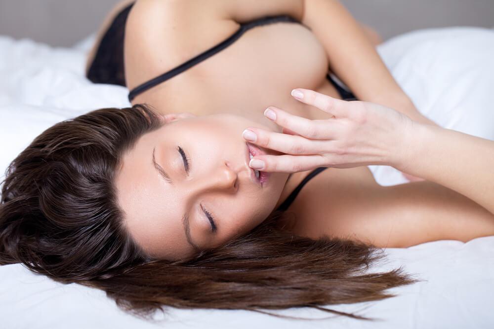 Mujer en la cama con los ojos cerrados y la cara de placer