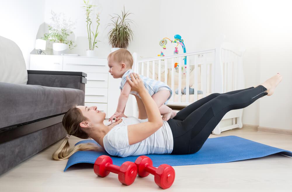 Mujer de 35 años con su bebé haciendo ejercicio