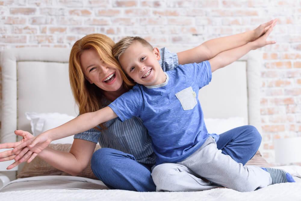 Madre de más de 35 años y su hijo de 8 riendo sobre la cama con los brazos estirados