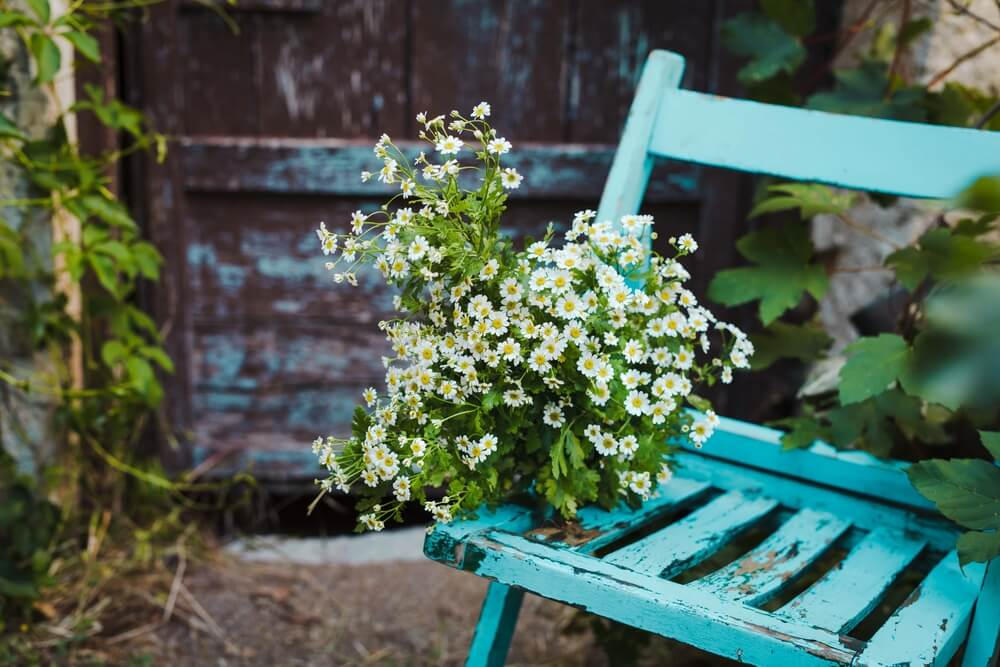 Silla de madera azul con flores.