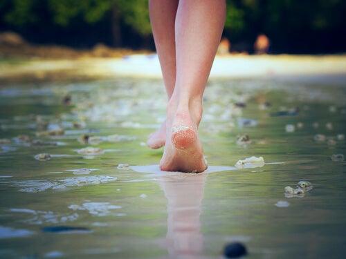 Pies descalzos caminando por la orilla de una playa.