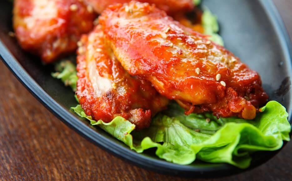 Alitas de pollo con salsa y lechuga.