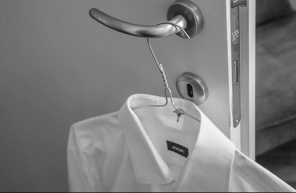 Una camisa blanca colgada del manillar de la puerta en blanco y negro.