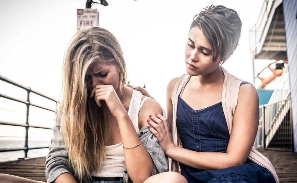 Chica consolando a su amiga.