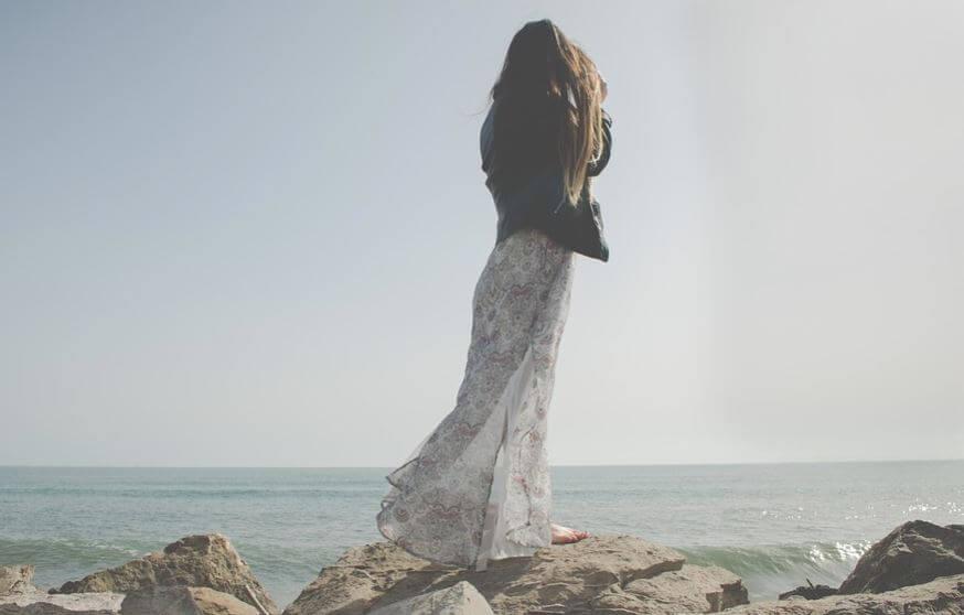 Chica en el mar con vestido largo.