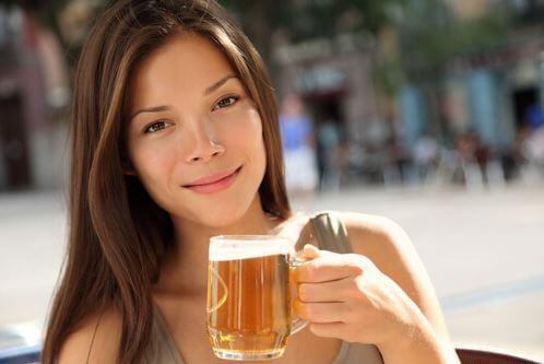 Chica joven bebiendo un vaso de cerveza.
