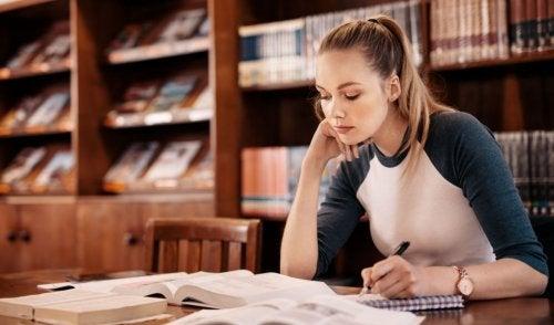 Chica joven rubia estudiando en la biblioteca.