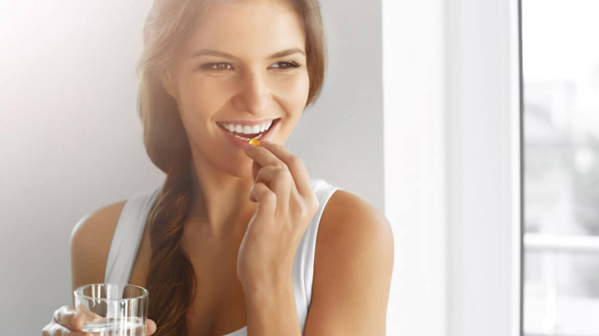 Una chica sonriente toma una pastilla.