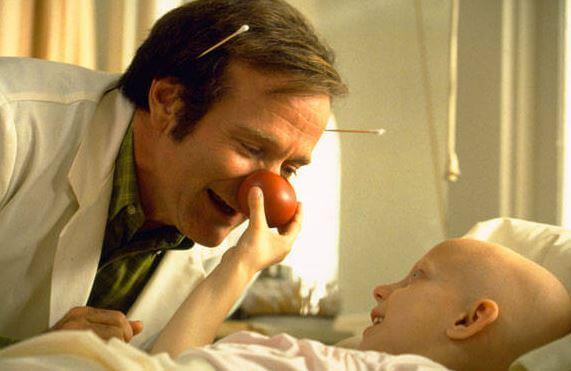 Fotograma de la película Pach Adams niño rie junto al doctor con nariz de payaso. afrontando las dificultades