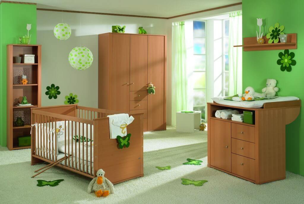 Habitación de bebé decorada con tonalidades verdes y muebles de madera.