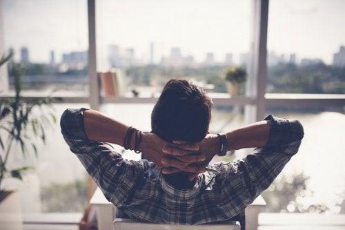 Un hombre mirando por la ventana descansando.
