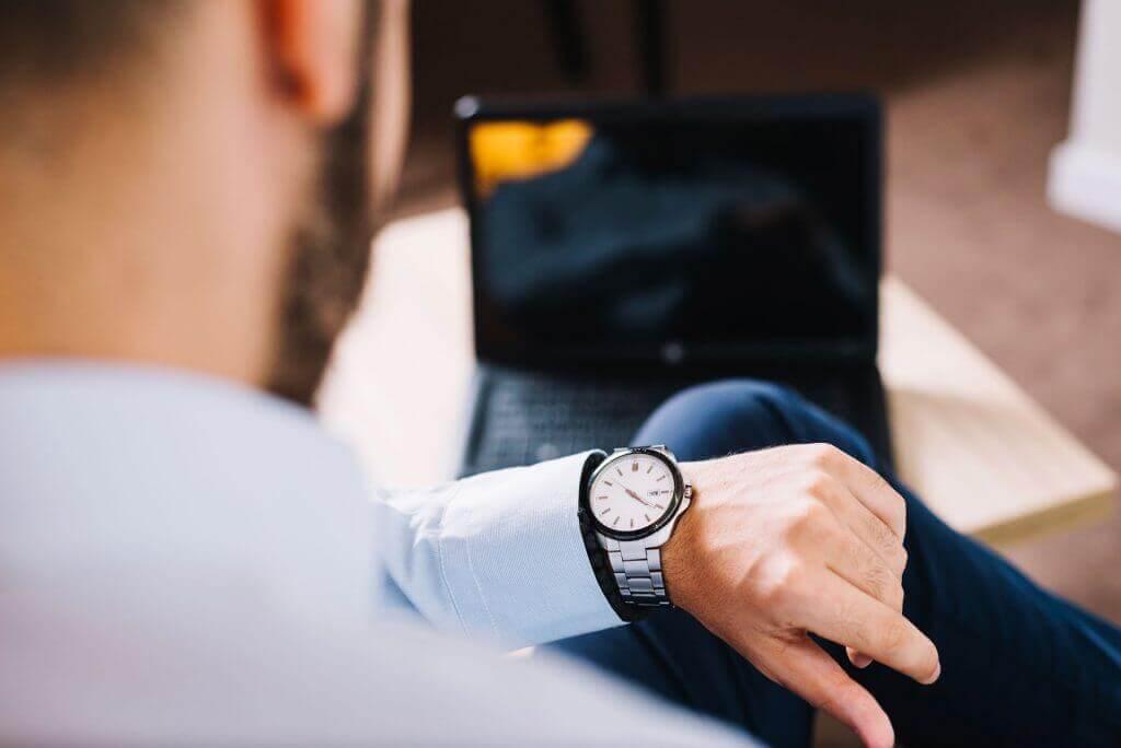 Hombre mirando reloj de pulsera.