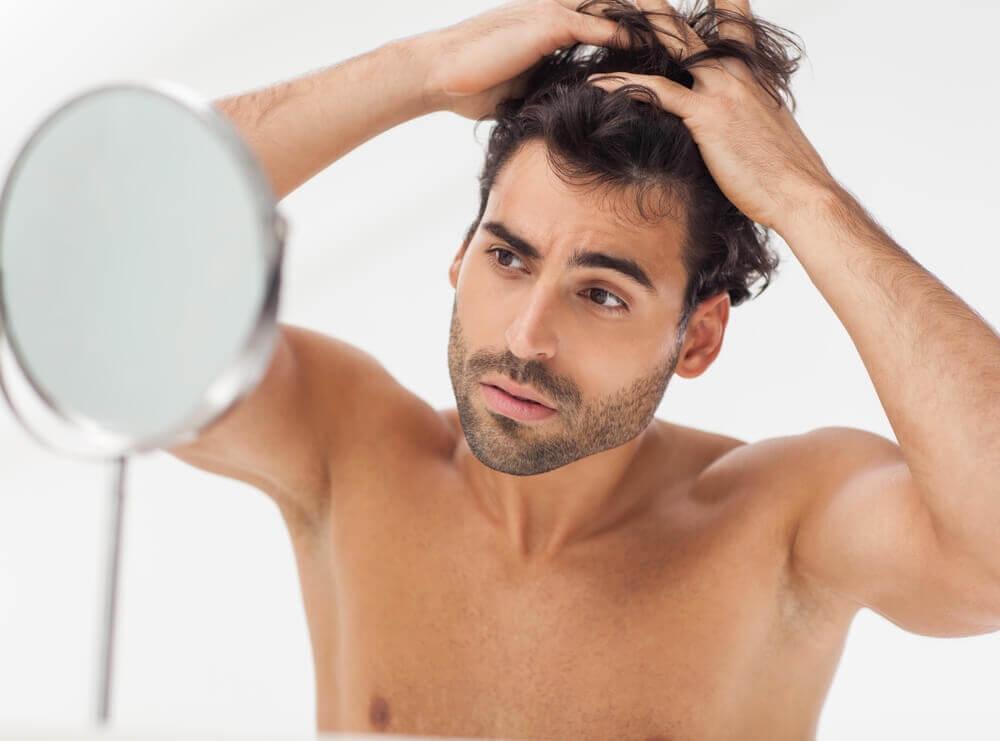 Hombre mirándose frente al espejo.