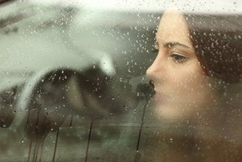Mujer aceptando ruptura de pareja mirando por una ventana