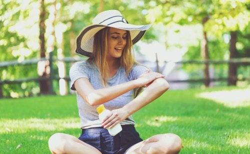 Mujer aplicándose crema solar.
