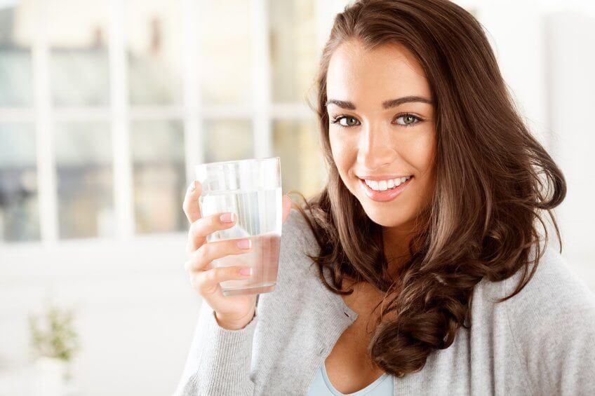 Mujer con vaso de agua en la mano representando consumir agua
