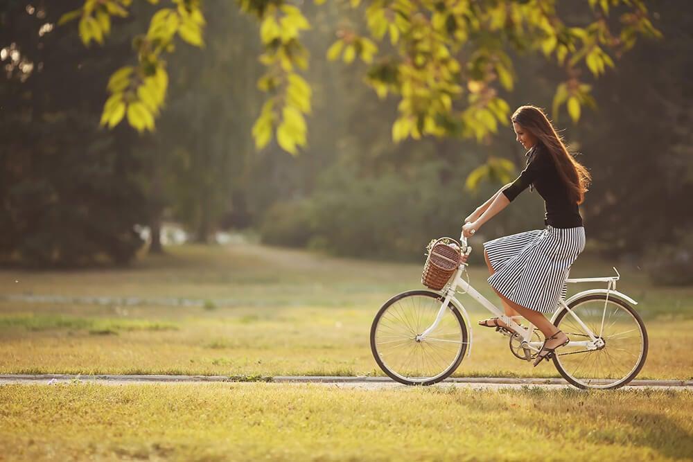 Mujer en bicicleta para aumentar la actividad física.
