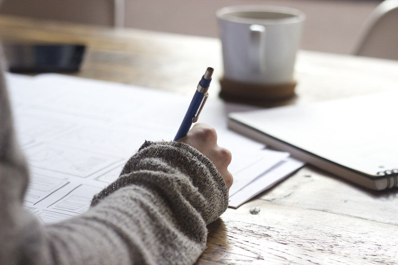 Mujer escribiendo propósitos en una libreta.