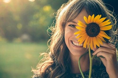 Mujer feliz con girasol que intenta vivir mejor