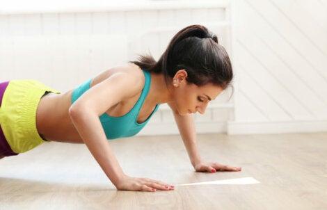 Mujer haciendo flexiones en el suelo.