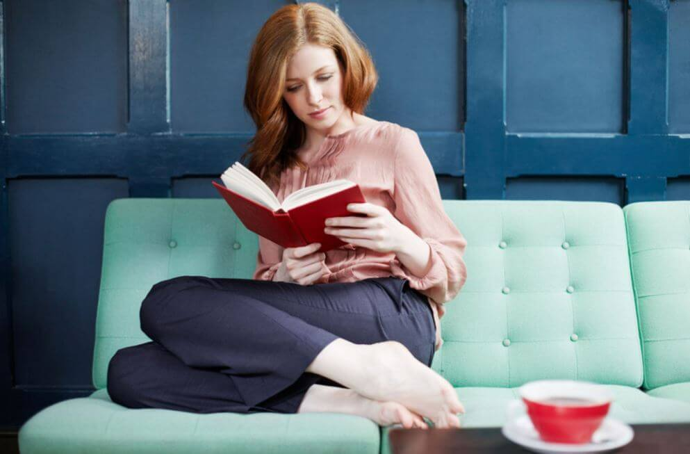 Mujer leyendo sola en casa.