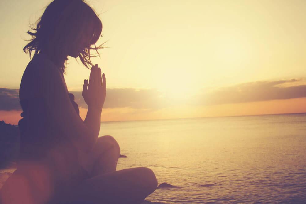 Mujer meditando al amanecer.