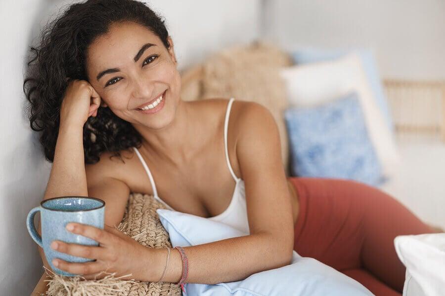 Mujer sonriendo con una taza en la mano.