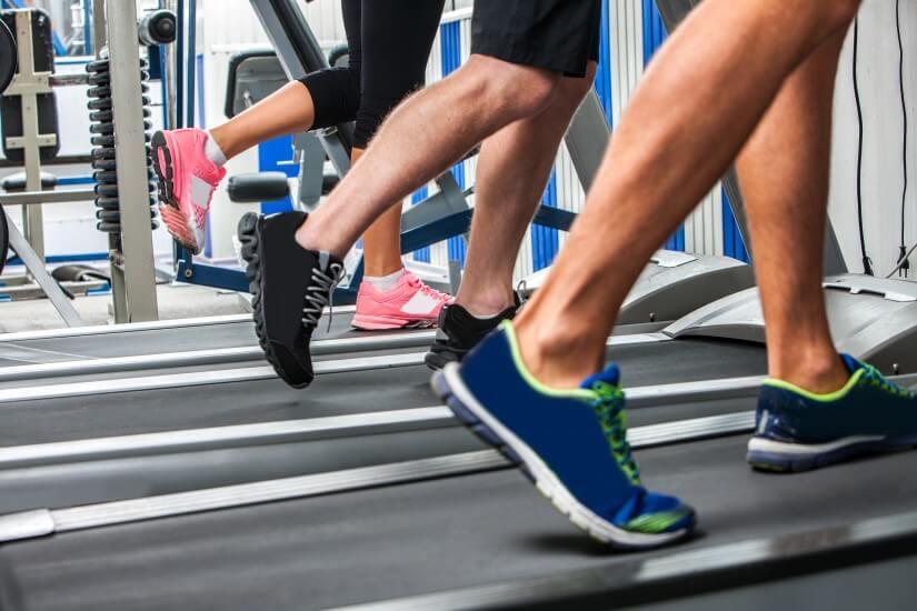 Personas en el gimnasio corriendo por los aeróbicos