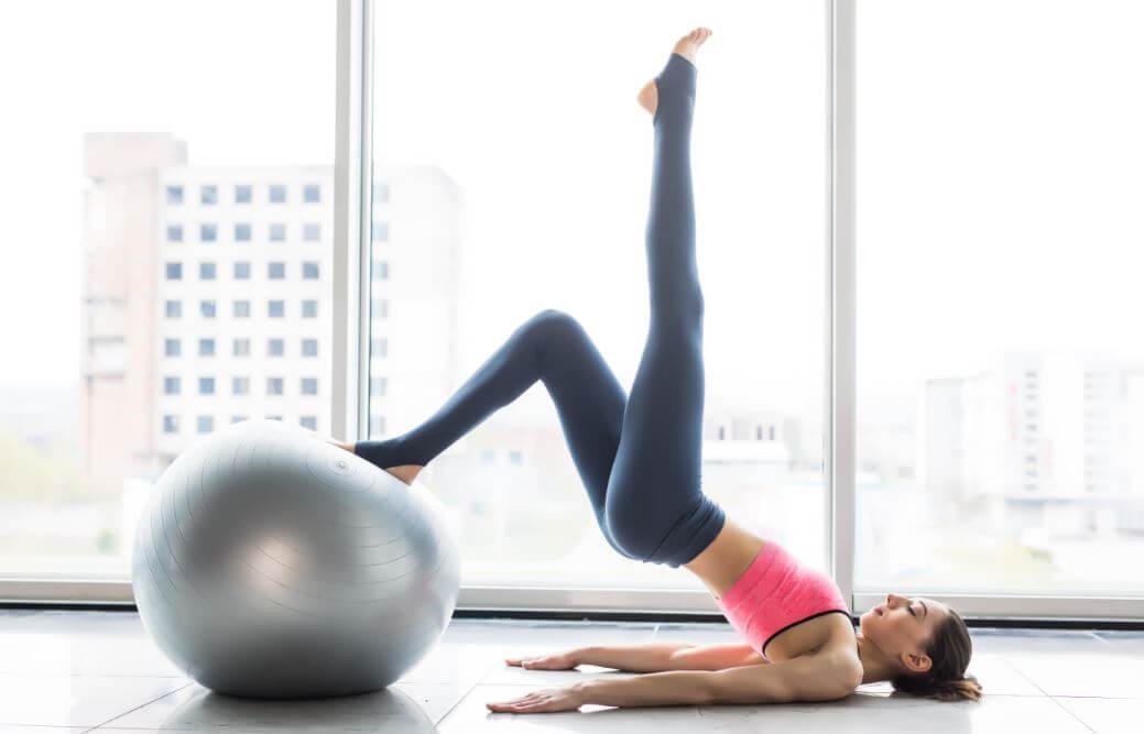 Mujer estirando una pierna con la otra sobre una bola deportiva.