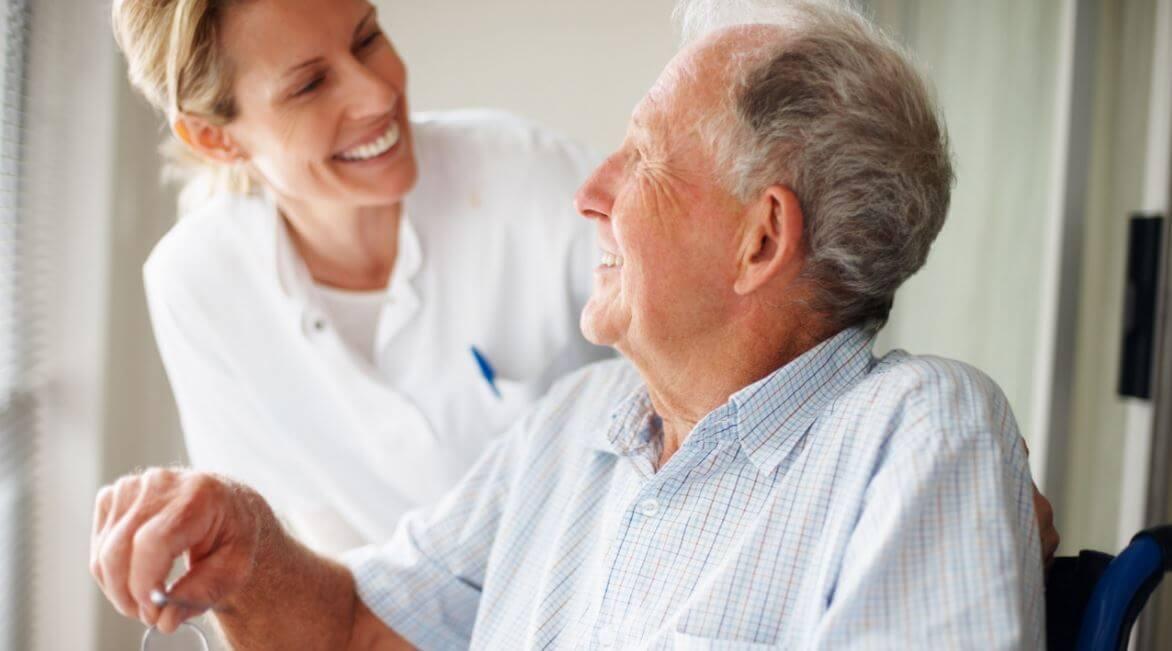 Señor mayor ríe junto a su enfermera afrontando las dificultades
