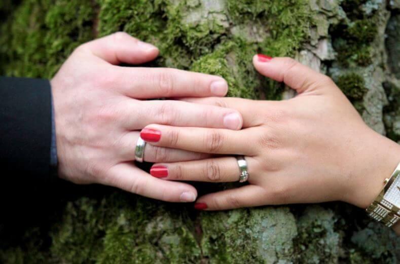 Una pareja de la mano el día de su boda.