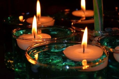 Mesa decorada con velas flotantes en agua.