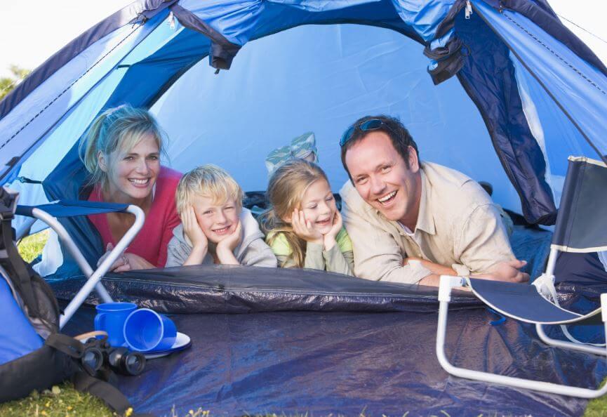 Familia de 4 miembros acampando en el jardín para compartir una experiencia juntos