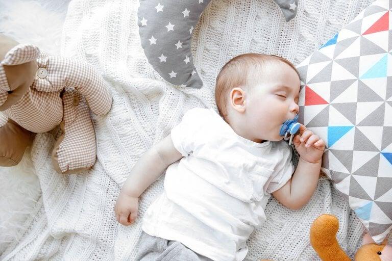 Bebé durmiendo con sus peluches y chupete.