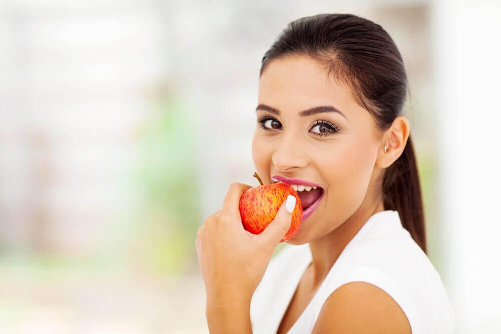 Chica comiendo una manzana que tiene efecto saciante